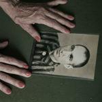 Manos de Maggie Perlado sobre una fotografía de retrato de su padre, también deportado